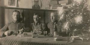 """W centralnej części ziemianki stoi pięknie udekorowana choinka, a oficerowie wznoszą toast ciemnym piwem. Na innym zdjęciu żołnierze dumnie prezentują """"świąteczne"""" prezenty- likier Abtei -Likor, wieki karton z cygarami i cały talerz kiełbasy. Wyższe szarże- dowództwo kompani- pozuje przy przykrytym obrusem stole i szklaneczce piwa Beck."""